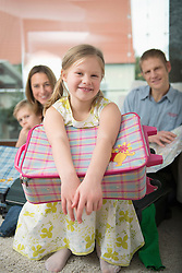 Family planning vacation, girl sitting in foreground with bag on knees
