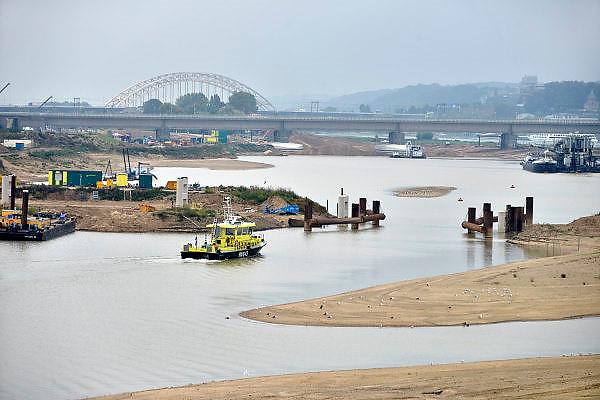 Nederland, Nijmegen, 27-9-2014 Aan de overkant van de Waal bij Lent wordt druk gewerkt aan het creeren van een nevengeul in de rivier om bij hoogwater een betere waterafvoer te hebben. Het is een omvangrijk project waarbij onder meer de pijlers van het spoorviaduct een bredere basis moeten krijgen omdat die straks in de loop van het water staan. Ook de n325 die vanaf de Waalbrug naar Arnhem loopt moet over 400 meter opnieuw worden aangelegd omdat het talud vervangen wordt door pijlers. De weg wordt via een bypass omgeleid. Het dorp veurlent komt op een kunstmatig eiland te liggen. Inmiddels begint de nieuwe kade aan de noordkant van deze geul vorm te krijgen. Ruimte voor de rivier, water, waal. In de nieuwe dijk wordt een drempel gebouwd die stapsgewijs water doorlaat en bij hoogwater overloopt. Measures taken by Nijmegen to give the river Waal, Rhine, more space to flow during highwater and to prevent the risk of flooding. Room for the river. Reducing the level, waterlevel. Foto: Flip Franssen/Hollandse Hoogte