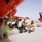 Engineering ground staff of the Red Arrows, Britain's RAF aerobatic team, rest in the shade before working on their Hawk jets.