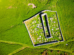 Aerial view from drone of St John's Church and Kirkyard overlooking  village of Gardenstown on Moray firth Coast in Aberdeenshire, Scotland, Uk