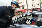 """March, 17th, 2020 - Paris, Ile-de-France, France: French police control of vehicles and inspection of valid papers allowing citizens to travel on the first day of a near total lockdown imposed in France. All journeys outside the home unless justified for essential professional or health reasons are outlawed. Anyone flouting the new regulations will be punished. This is the beginning of the most extreme measures so far in France to control the spread of the Coronavirus. The night before, President of France, Emmanuel Macron, said that citizens must stay at home from midday on Tuesday for at least 15 days. He said """"We are at war, a public health war, certainly but we are at war, against an invisible and elusive enemy"""". Nigel Dickinson"""