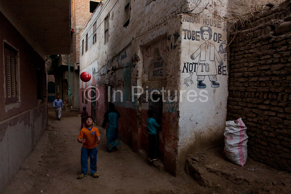 A young Egyptian boy throws his ball up in the air while playing football near a Shakepearean quote, written on the wall of a house in the village of Bairat on the West Bank of Luxor, Nile Valley, Egypt.