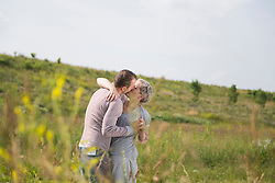 Mature couple kissing in field