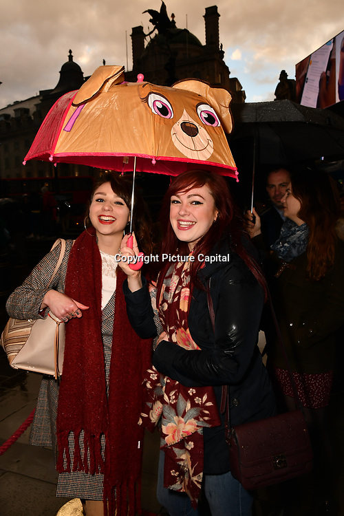 Theatre fans queuing with an umbrella outside The Comedy About a Bank Robbery at Criterion Theatre, Piccadilly Circus, London, UK. on 2nd April 2019.
