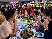 05 MARCH 2019 - BANGKOK, THAILAND:  A waiter brings a pile of stewed pork ribs to a table of Chinese tourists in the Ratchada Night Market. The Ratchada Night Market is the newest night market in Bangkok. It was originally a small night market popular with local people but now is tourism destination. Most nights the market is jammed with foreign tourists.   PHOTO BY JACK KURTZ