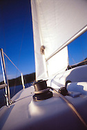 winch on sailboat with sail in background