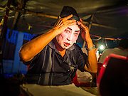 "06 DECEMBER 2015 - BANGKOK, THAILAND: A Chinese opera performer puts on his costume before going on stage at the Ruby Goddess Shrine in the Dusit district of Bangkok. Chinese opera was once very popular in Thailand, where it is called ""Ngiew."" It is usually performed in the Teochew language. Millions of Chinese emigrated to Thailand (then Siam) in the 18th and 19th centuries and brought their culture with them. Recently the popularity of ngiew has faded as people turn to performances of opera on DVD or movies. There are about 30 Chinese opera troupes left in Bangkok and its environs. They are especially busy during Chinese New Year and Chinese holidays when they travel from Chinese temple to Chinese temple performing on stages they put up in streets near the temple, sometimes sleeping on hammocks they sling under their stage.     PHOTO BY JACK KURTZ"