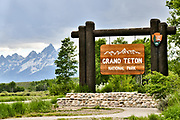 Park sign welcoming visitors to the Grand Teton National Park with Mount Moran and the Grand Teton mountains behind in Moran, Wyoming.