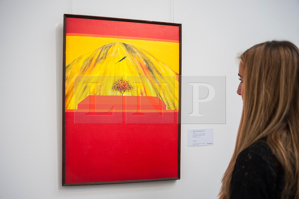 """© Licensed to London News Pictures. 02/10/2015. London, UK. A Sotheby's employee views """"Unititled, (Bird, Tree and Mountain)"""" by Jagdish Swaminathan (est. £60k - 80k) at the preview of Indian and Islamic Art Week at Sotheby's which runs from 2 to 7 October.  Photo credit : Stephen Chung/LNP"""