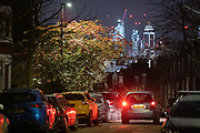 The glow of distant buildings overlooks the red brake lights of a passing car and other parked vehicles in a dark residential street in Herne Hill, south London on 21st January 2021, in London, England.