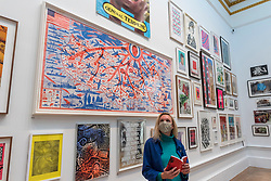 "© Licensed to London News Pictures. 28/09/2020. LONDON, UK. A staff member poses in front of ""The American Dream"" by Grayson Perry, RA.  Preview of the Summer Exhibition at the Royal Academy of Arts in Piccadilly which, due to the Covid-19 lockdown, is taking place for the first time in the autumn.  Over 1000 works in a range of media by Royal Academicians, established and emerging artists, feature in the exhibition which runs from 6 October 2020 – 3 January 2021.  Photo credit: Stephen Chung/LNP"
