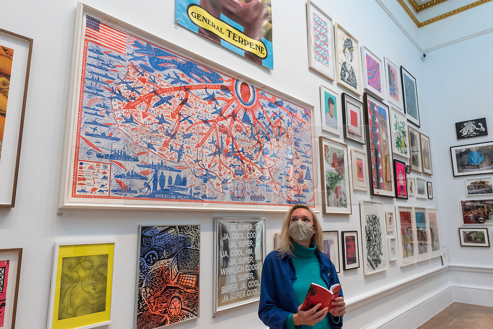 """© Licensed to London News Pictures. 28/09/2020. LONDON, UK. A staff member poses in front of """"The American Dream"""" by Grayson Perry, RA.  Preview of the Summer Exhibition at the Royal Academy of Arts in Piccadilly which, due to the Covid-19 lockdown, is taking place for the first time in the autumn.  Over 1000 works in a range of media by Royal Academicians, established and emerging artists, feature in the exhibition which runs from 6 October 2020 – 3 January 2021.  Photo credit: Stephen Chung/LNP"""