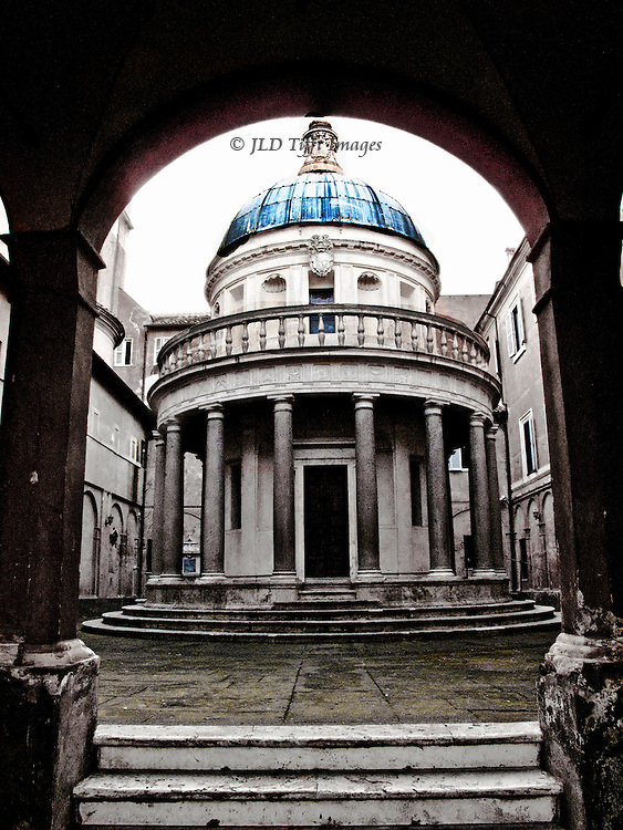 Tempietto di Bramante, in courtyard of San Pietro di Montorio. 1502, on the site where St. Peter is supposed to have been crucified.  Round, Doric order, dome, seen through arched entrance.