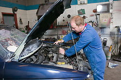 Car mechanic working on the engine of a car,