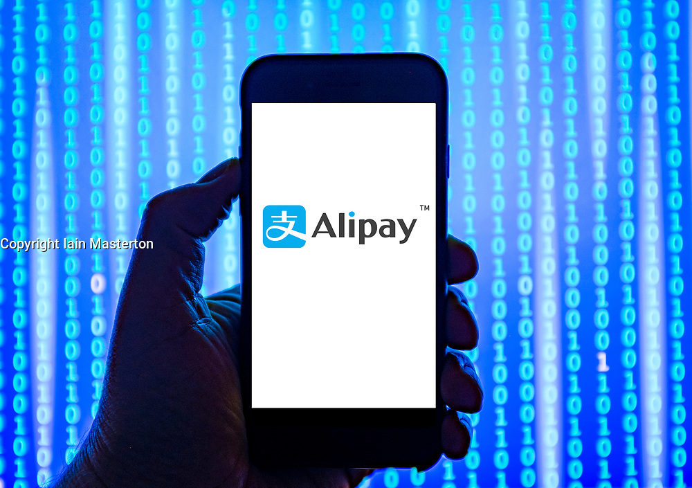 Person holding smart phone with Alipay third-party mobile and online payment platform logo displayed on the screen. EDITORIAL USE ONLY
