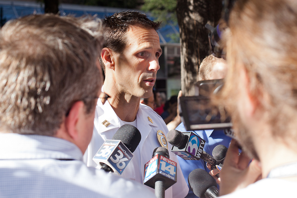 A chief for CMPD is interviewed by local news outlets during a march and protest in front of Bank of America headquarters in uptown Charlotte, NC.