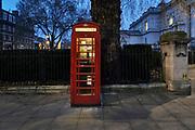 Engeland, Londen, 10-4-2019 Straatbeeld van het centrum van de stad. Een traditionele rode telefooncel in de avond. Deze telefooncellen blijven staan uit historische overwegingen. Geschiedenis,telecommunicatie,telefoon,telefoneren ,verleden,vroeger,historie Foto: Flip Franssen