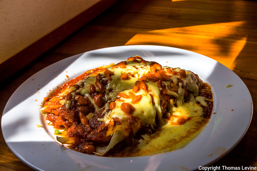 Enchilada's served with cheese, chili sauce filling a white plate with high lighted areas and shadows on a wood table. RAW to Jpg