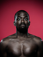 one young dumb african man topless portrait in studio on red background