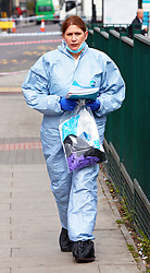 © under license to London News Pictures. 30/03/2011.  Police forensic officers investigate the Stockwell Food & Wine shop, Stockwell Road, Brixton where a 5 year old girl and a 35 year old man were shot last night. . Photo credit should read Cliff Hide/LNP..