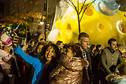 New York, NY – 27 November 2019. Thousands of spectators packed the streets around the American Museum of Natural History to see the inflation area for the balloons for Macy's Thanksgiving Day Parade. A woman and a girl pose for a selfie in front of Spongebob Squarepants.