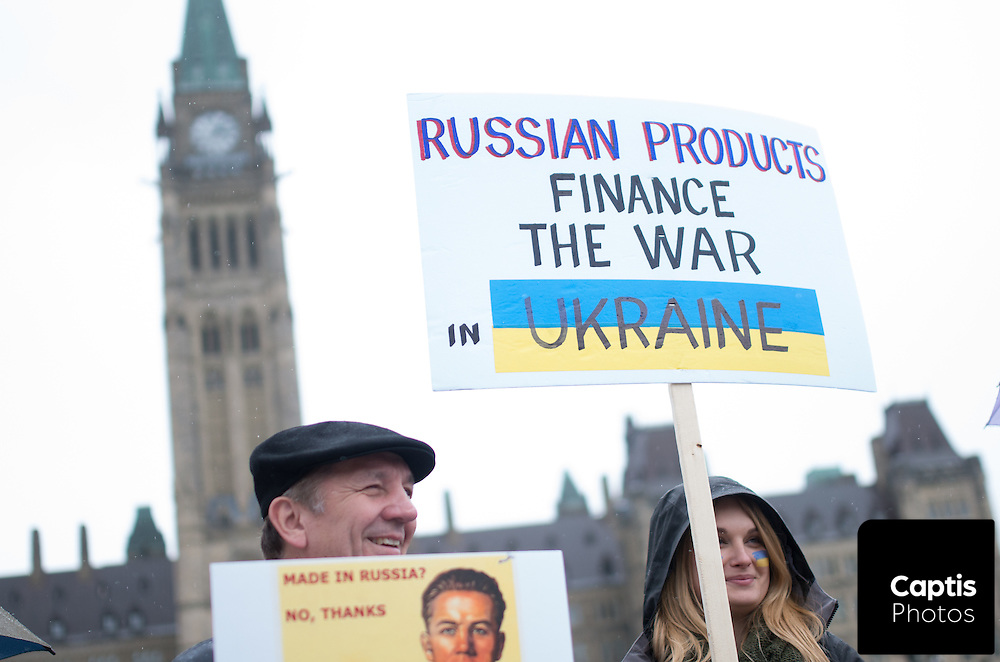 Protesters stand in front of Parliament with signs asking Canadians to boycott Russian products. April 26, 2014.