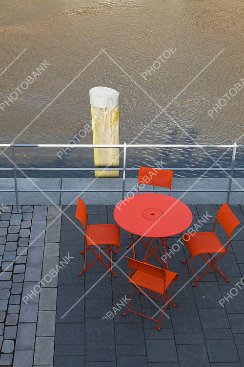 Colorful chairs on the shore of the canal