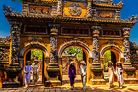 Vietnamese women wearing the traditional Ao Dai costume walk through the North Gate of The Imperial City, a walled palace within the citadel of the city of Huế which is the former imperial capital of Vietnam. Hue, Central Vietnam.