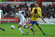 Swansea city's Jonathan de Guzman is challenged by Arsenal's Mathieu Flamini. Barclays Premier league, Swansea city v Arsenal at the Liberty Stadium in Swansea on Saturday 28th Sept 2013.  pic by Andrew Orchard, Andrew Orchard sports photography.