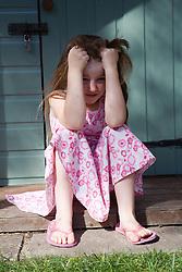 Little girl feeling upset in the garden,