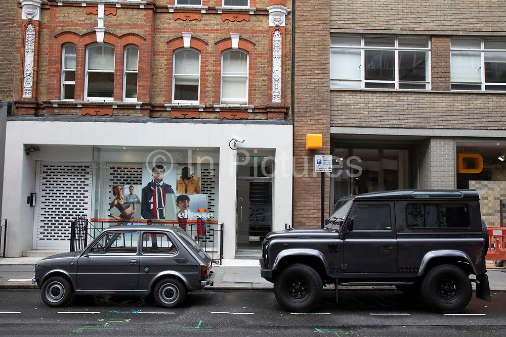 A small Fiat 126 car and a large Land Rover Defender give a strong and weak contrast in size, style and scale in London, England, United Kingdom. Vehicles like SUVs and 4x4s are recieving a lot of criticism, particularly in the city for taking up too much space as they become larger in design, and questioning their ecological credentials.