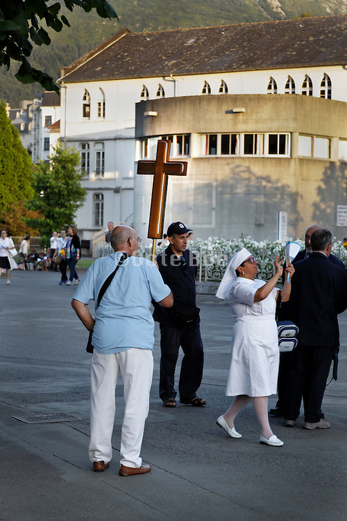 getting ready for the candle parade held every evening by the basilica of the immaculate conception Notre Dame of Lourdes in France