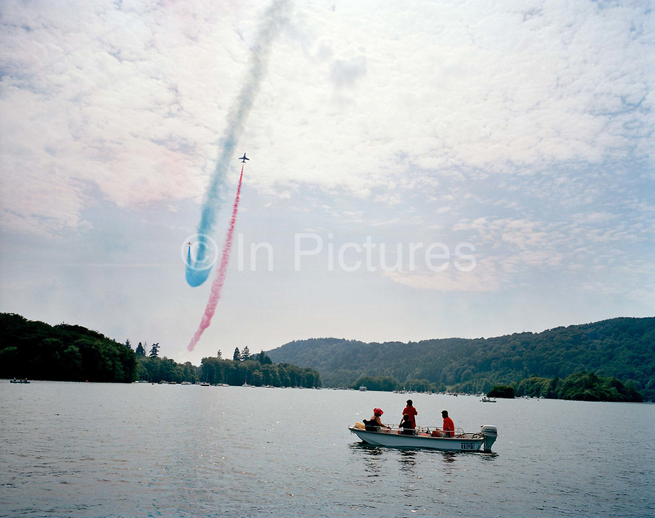 The Red Arrows, Britain's RAF aerobatic team, perform their public display over a lake and boating landscape. A family stay still below the elite team as they perform their display on one of the UK's most beautiful locations in norhern England. The team are using the lake as a reference point as display datum (centre) during their display, a show-stopping manoeuvre of their 25-minute air show display routine. 'Datum' is an axis on which the Red Arrows focus their displays, from where the whole show is visible at the crowd's centre. The lake is but one of a series of datum points selected by the team leader as a geographical point from which to navigate. Since 1965 the squadron have flown over 4,000 shows in 52 countries and are an important part of Britain's summer events where aerobatics aircraft perform their manoeuvres in front of massed crowds.