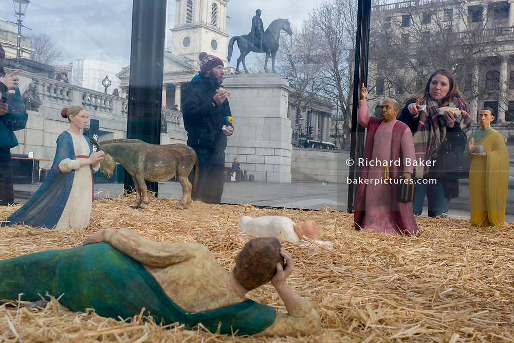 The annual Christmas nativity scene entitled 'Christmas Crib' by the artist Tomoaki Suzuki and located in Trafalgar Square, attracts interest from onlookers, on 13th December 2019, in London, England.