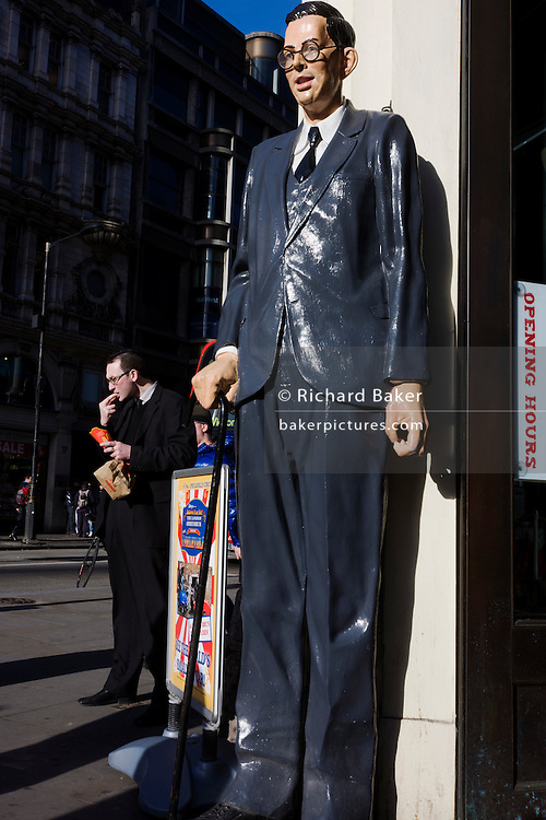 Scale model of world's tallest man Robert Pershing Wadlow in London street with similar-looking man eating junk food...Robert Pershing Wadlow (February 22, 1918 - July 15, 1940) is the tallest person in history. He reached 8 ft 11.1 in (2.72 m)[2][3] in height and weighed 485 lb (220 kg) at his death at age 22. His great size and his continued growth in adulthood was due to hypertrophy of his pituitary gland which results in an abnormally high level of human growth hormone. He showed no indication of an end to his growth even at the time of his death.