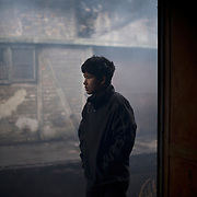 A young Afghan migrant stands a the door of one of the abandoned warehouses near Belgrade's main railway station. The large majority of the more than a thousand refugees living here, comes from war torn Afghanistan and neighbouring mountains areas of Pakistan.