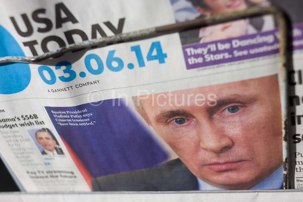 The face of Russian President Vladimirovich Putin appears on the front page of American global newspaper USA Today. The detail shows us Putin's face looking out from under the rack on sale outside a central London newsagent that sells titles from around the world. The date shows that page 1 is on the the sixth of March 2014 - 03.06.14 - when uncertainty of the Russian's annexation of the Crimea made headlines around the globe. Propaganda came from both sides as each nation tried to persuade other countries to back their own actions. Vladimir Putin has been the President of Russia since 7 May 2012. He previously served as President from 2000 to 2008, and as Prime Minister of Russia from 1999 to 2000 and again from 2008 to 2012.