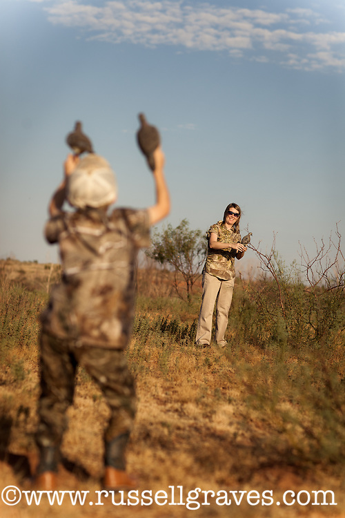 HUNTER WEARING REALTREE CAMOUFLAGE PUTTING OUT DOVE DECOYS