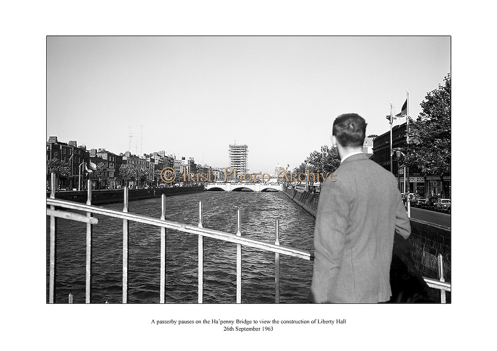 A passerby pauses on the Ha'penny Bridge to view the construction of Ireland's newest skyscraper Liberty Hall.<br /> <br /> 26th September 1963<br /> <br /> 26/09/1963