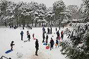 People and families at play in Kings Heath Park head out to enjoy the heavy snow fall on Sunday 10th December 2017 in Birmingham, United Kingdom. Deep snow arrived in much of the UK, closing roads and making driving treacherous, while many people simply enjoyed the weather.