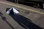 A person's shadow with a discarded broken umbrella in Charing Cross Road, central London.