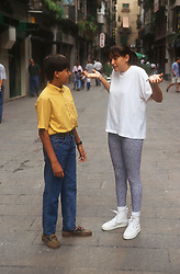 Woman standing in street asking directions from young boy in Gerona; Catalunya,
