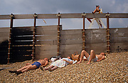 Three bathers lie on the shingle in the lee of a groyne, a wooden screen from the fresh breeze that has been written on by unknown people having scrawled their names and a noughts and crosses puzzle written in chalk. One person wears his socks in true English style and the lady in the middle has her bag containing possessions near her head. Above them sits a lifeguard on a pair of high steps, peering along the beach with a pair of binoculars. Meanwhile, a lone seagull wheels around the coastal thermals and is caught between the wooden slats of the groyne.