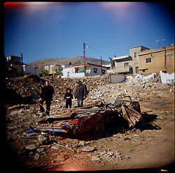 A family is seen among the rubble after heavy fighting between Hezbollah and Israel, Aytaroun, Southern Lebanon, Oct. 23, 2006.