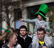 Boy wearing leprechaun hat on man's shoulders, at Dublin St. Patrick's Day parade