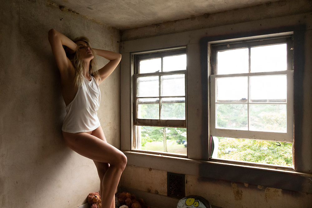Sexy woman in a t-shirt leaning up against a wall in an attic