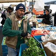 Nederlands Amsterdam Bijlmermeer 29 maart 2011 20110329 Wijkmarkt Kraaiennest, man van surinaamse afkomst verkoopt exotische groente en fruit surinaamse produkten op de markt. , werken, werkend, werkende, werkgelegenheid, werkzaam, werkzaamheden, werkzaamheid, werkzame, westerse allochtonen, westerse allochtoon, wijk k, wijk kraaiennest, wijkmarkt, winkelen, work, working class, zuid oost , plezier in het werk hebben, prioriteitswijk, prioriteitswijken, probleembuurt, probleemwijk, probleemwijken, productief zijn, productieve, schijf van 5, spullen verkopen, straatbeeld, straatgezicht, streetscene, surinaams, surinaamse produkten, surinamer, surinamers, tropische, uit het buitenland, verdienen, verhandelen, vlijtig, vlijtige, Voedingsmiddelen, vogelaarbuurt, vogelaarbuurten, vogelaarwijk, vogelaarwijken, weekmarkt, werk Foto: David Rozing