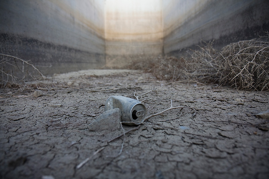 A metal beer can lies in the dried patterned mud below the retention dam at the Boulder Reservoir outside Boulder, Colorado. The water retreats from the dam by the end of Summer.