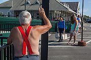 A man in red suspenders watches passengers board the ferry to Vinalhaven in Rockland, Maine.