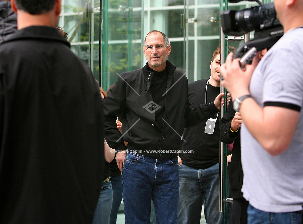 Steve Jobs, Apple Computer, Inc. chief executive officer, center, stands outside the new Apple Store in New York moments prior to the grand opening on Friday, May 19, 2006. Apple Computer Inc., maker of the iPod music player, opened a 24-hour subterranean store in New York City, marking five years in retailing with an outlet built beneath a 32-foot glass cube.
